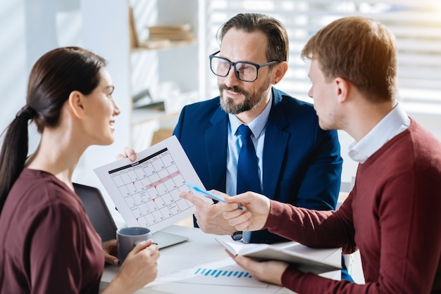 Month schedule. attractive appealing three colleagues discussing schedule while woman drinking coffee and man pointing with pen