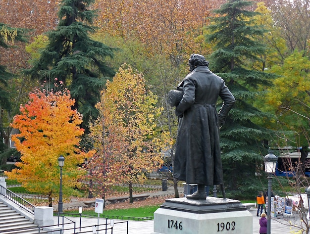 Monument of francisco de goya facing the north facade of prado museum with colorful fall foliage, madrid, spain