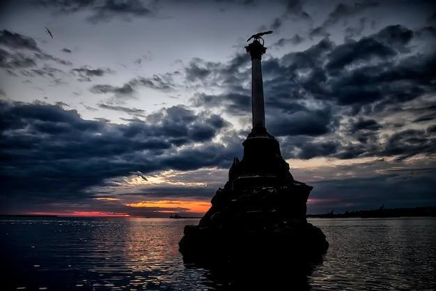Памятник затонувшим военным кораблям в севастопольской бухте на крымском полуострове. вечерний пейзаж. статуя на фоне заката с текстурированным небом и черным морем в лучах заходящего солнца. уникальные места россии