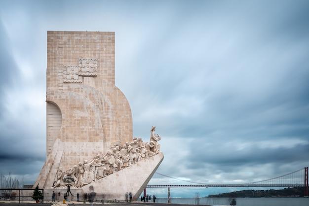 Памятник открытиям (pedrao dos descobrementos) на северном берегу реки тежу в лиссабоне, португалия, на фоне моста 25 апреля.