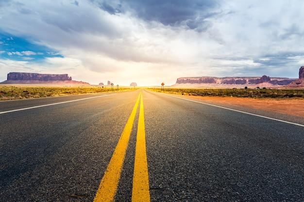 日没時に地平線に向かうモニュメントバレーの道。