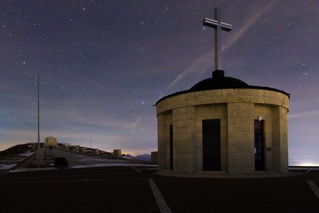 Памятник на фоне звездного неба. вид на военный мемориал горы граппа, итальянский ориентир.