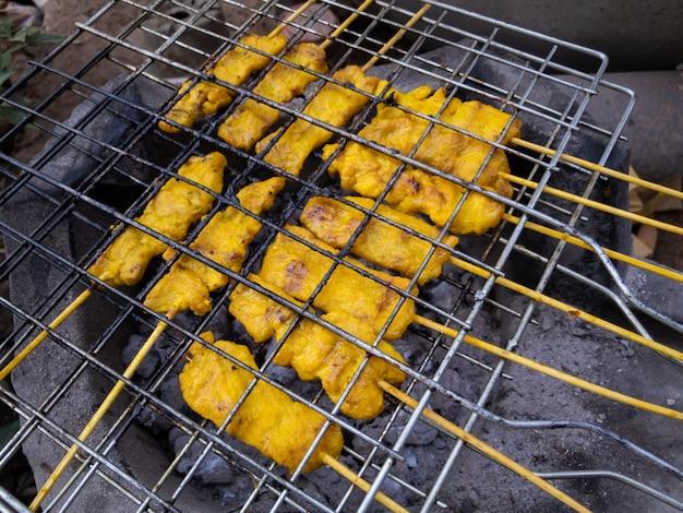 「moo sa tek」と呼ばれる黄色のハーブを使った伝統的なタイのポークバーベキュー。ポークバーベキューは非常に有名なタイの屋台の食べ物です。黄色の豚肉バーベキューをクローズアップ。