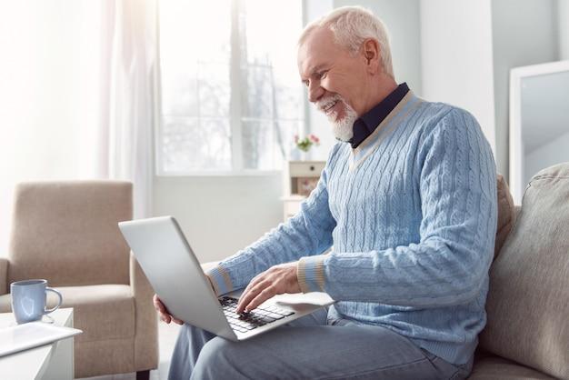 気分を高めるチャット。陽気な年配の男性がソファに座ってラップトップで幸せそうに笑いながらメールを入力