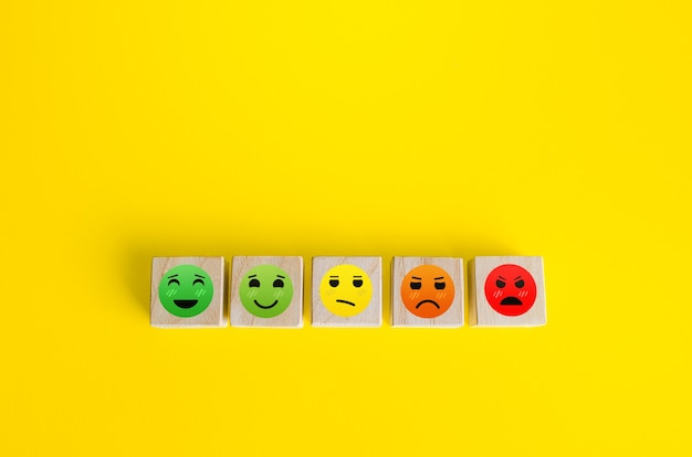 Mood faces from happy to angry on wooden blocks concept of rating review