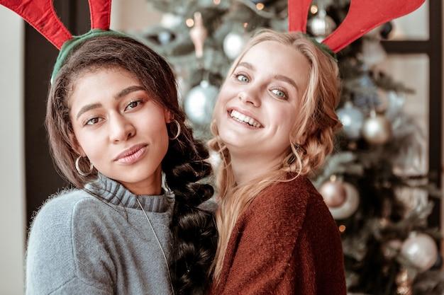 休日の気分。お互いに抱き合って、クリスマスツリーとの親密な友情を示す楽しい長髪の女の子