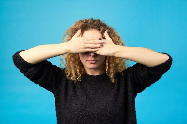 기분. 보고 싶지 않아요 손으로 그녀의 눈을 덮고 빨강 머리 곱슬 소녀. 파란색 배경에 촬영 스튜디오입니다.