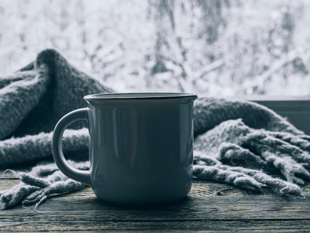 Mood, lifestyle, still life concept. hot cup of coffee and cozy grey scarf on vintage windowsill against snow landscape from outside. relaxing winter day at home. scandinavian hygge style. soft focus