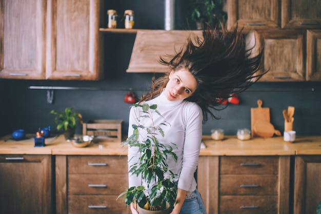 Mood portrait of beautiful young woman with scattered hair and tilted head holding pot with flower.