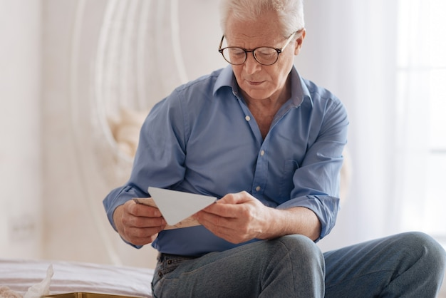 Moody cheerless aged man holding an old letter and reading it while being nostalgic about his past