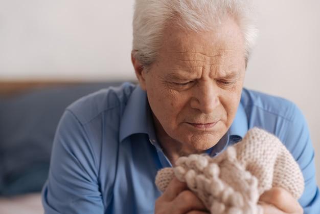 Муди в депрессии пожилой мужчина смотрит на куртку своей жены и скучает по ней, находясь в горе