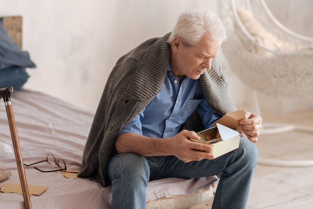 Moody depressed senior man holding a box and taking a letter out of it while sitting on the bed