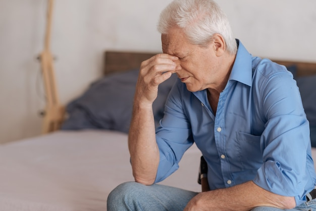 Moody grey haired aged man sitting on the bed and holding his nasal bridge while being in depression