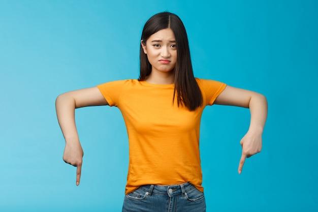 Муди грустная азиатская брюнетка в желтой футболке недовольно ухмыляется, хмурясь, озабоченно, жалуясь, указывая вниз указательными пальцами, показывая нижнюю рекламу расстроенной, ревнивую, чувствуя сожаление.