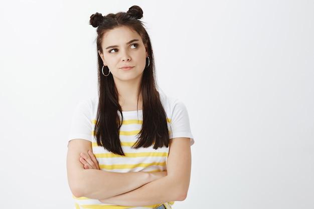 白い壁にポーズをとって不機嫌そうなスタイリッシュな若い女性