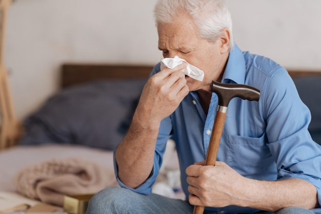 Moody unhappy aged man holding a paper tissue and blowing his nose while crying