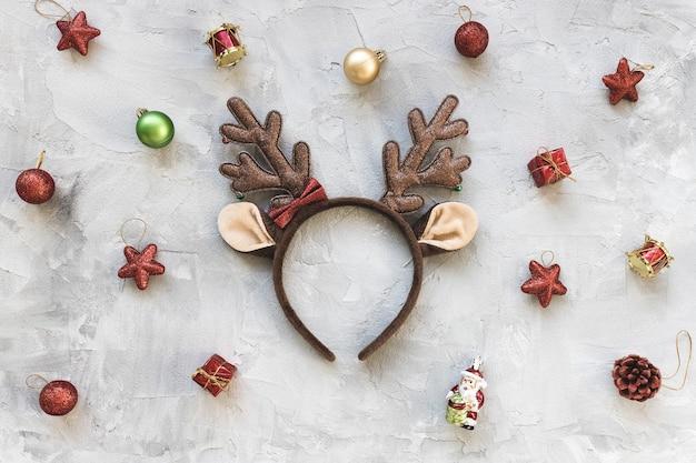 鹿の衣装のハンドバンドと休日の装飾と不機嫌そうな冬の休日の赤と白の背景。お祝いの抽象的な背景。クリスマスのお祝い、新年会のコンセプト