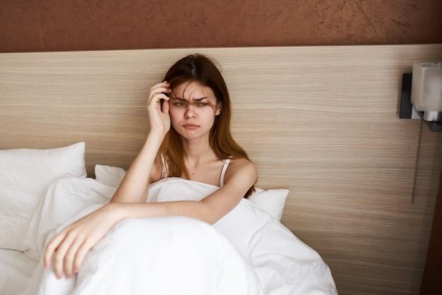 不機嫌そうな若い女性がベッドに座っている