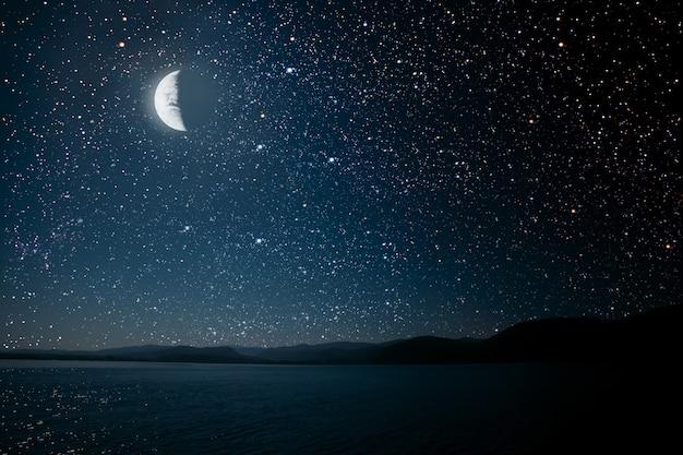 밝은 밤 별이 빛나는 하늘을 배경으로 달이 바다에 반사되었습니다.