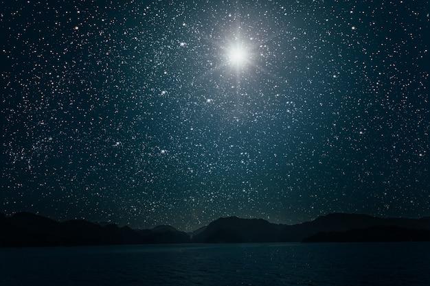 海に映る明るい夜の星空を背景にした月。