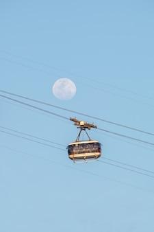 브라질 리우데자네이루의 달과 슈가로프 케이블카 - 2021년 8월 20일: 리우데자네이루의 아름다운 푸른 하늘에 있는 달과 슈가로프 케이블카.