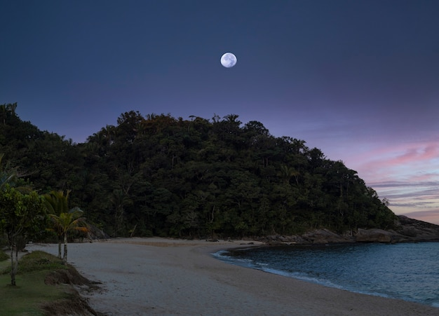 달이 마지막 일몰 순간에 브라질 상파울루 주레이아 해변에 나타납니다.