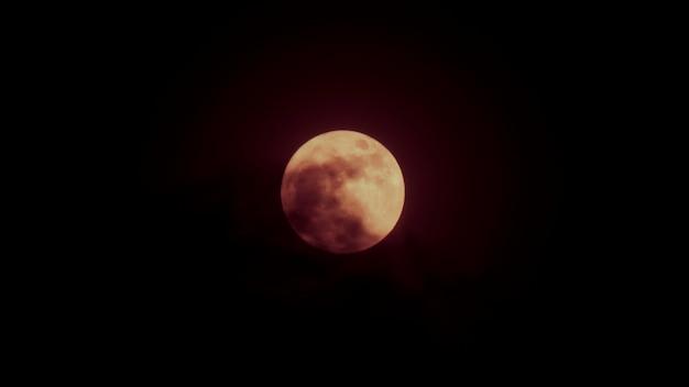 Луна ночью частично закрыта облаком. полная луна с драматическими облаками в ночном небе.