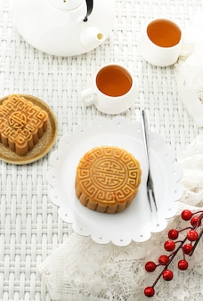 Moon cake (mooncake) chinese dessert snack during lunar new year mid autumn festival. served with tea. white concept asian bakery for mid autumn festival