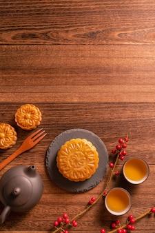 月餅の月餅のテーブルセッティング – 木の背景に茶碗を置いた中国の伝統的な菓子、中秋節のコンセプト、平面図、平置き