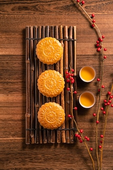 Moon cake mooncake table setting - chinese traditional pastry with tea cups on wooden background, mid-autumn festival concept, top view, flat lay