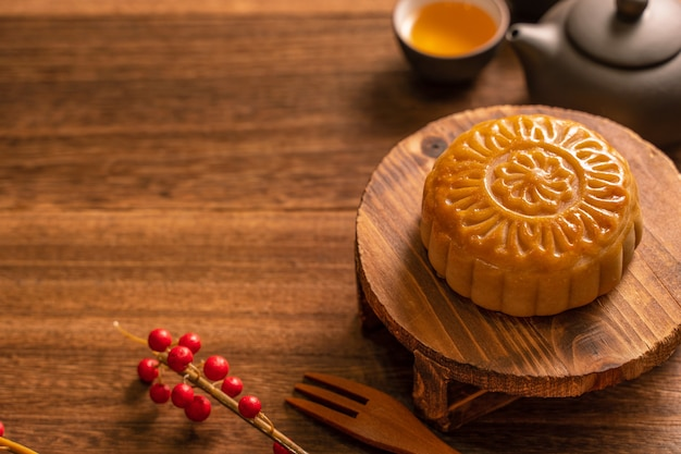 Moon cake mooncake table setting - round shaped chinese traditional pastry with tea cups on wooden background, mid-autumn festival concept, close up