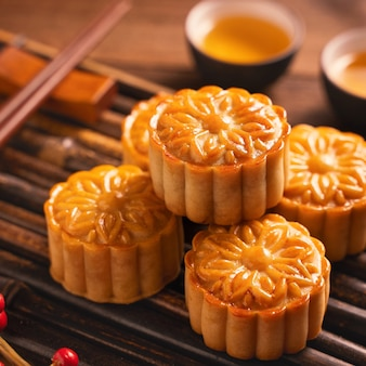 Moon cake mooncake table setting - round shaped chinese traditional pastry with tea cups on wooden background, mid-autumn festival concept, close up.