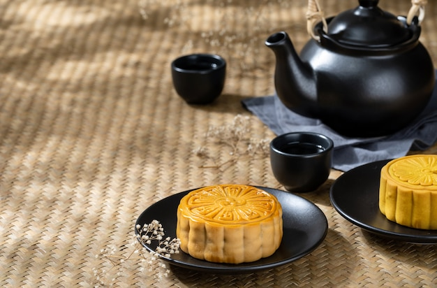 Moon cake with cup of hot tea on the the wooden table background with copyspace for your text