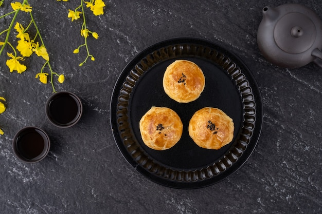 Moon cake yolk pastry, mooncake for mid-autumn festival holiday, top view design concept on dark wooden table with copy space, flat lay, overhead shot