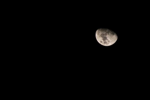 月。闇の背景に包まれたハーフムーン