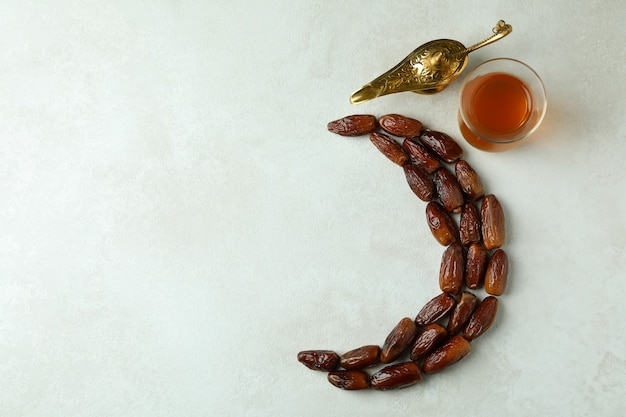 Moon made of dates, tea and ramadan lamp on white textured surface