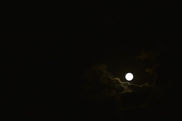 The moon shines through the clouds in the sky at night