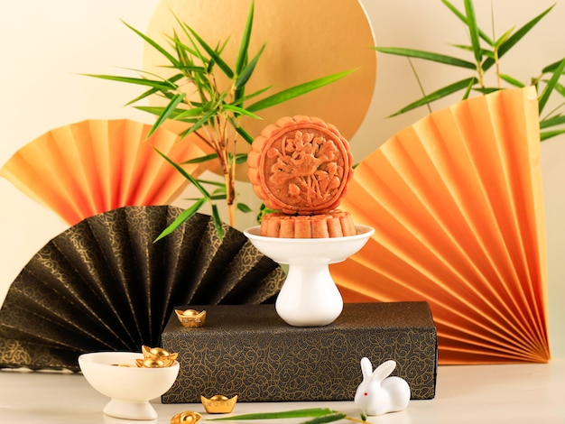 Mooncake concept on light background with bamboo. yellow concept moon cake on mid autumn festival. mooncake popular as kue bulan.