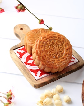 Mooncake on light pink background with pink flower. concept moon cake on mid autumn festival or chinese new year (imlek). mooncake popular as kue bulan.