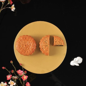 Mooncake on light pink background with pink flower. concept moon cake on mid autumn festival. mooncake popular as kue bulan.