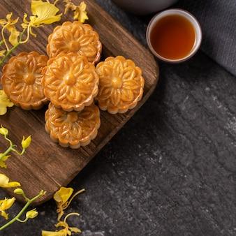 문케이크, 중추절을 위한 월병, 차와 노란색 꽃이 있는 검은 슬레이트 테이블에 전통 축제 음식의 개념은 닫히고 공간을 복사합니다.