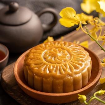 月餅、中秋節の月餅、お茶と黄色い花が付いた黒いスレートテーブルの伝統的なお祭り料理のコンセプトをクローズアップします。