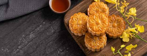 Mooncake, moon cake for mid-autumn festival, concept of traditional festive food on black slate table with tea and yellow flower, close up, copy space.