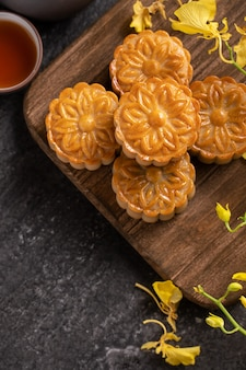 Mooncake, moon cake for mid-autumn festival, concept of traditional festive food on black slate table with tea and yellow flower, close up.