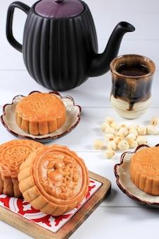 Mooncake на светлом фоне с чаем. концептуальный лунный торт на фестивале середины осени или китайском новом году (имлек). лунный пирог популярный как kue bulan. подается с китайским чаем