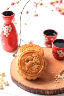 Mooncake on white background with pink flower. concept moon cake on mid autumn festival. mooncake popular as kue bulan
