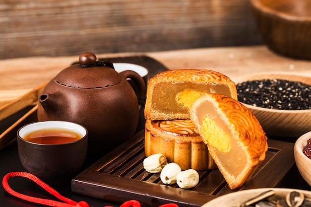 Традиционные mooncakes на сервировке стола с чашка.