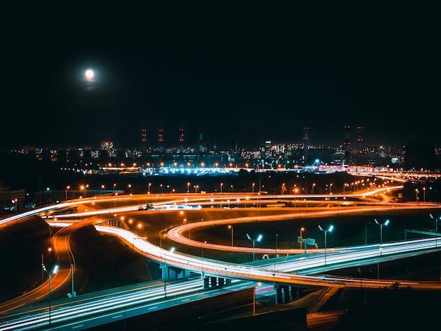 Лунный свет над ночной транспортной развязкой в промышленной зоне современного мегаполиса.