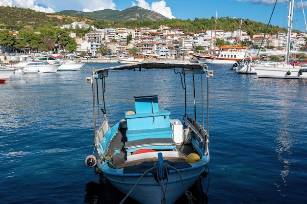 A moored boat made of wood in aegean sea port, buildings in neos marmaras, greece