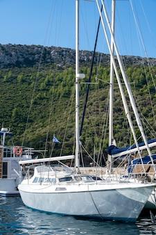 Пришвартованная лодка на причале в деревне, много зелени, зелень греции